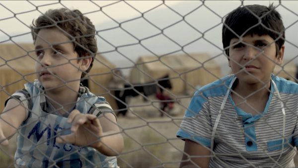 A photo of two young boys behind a chain link fence